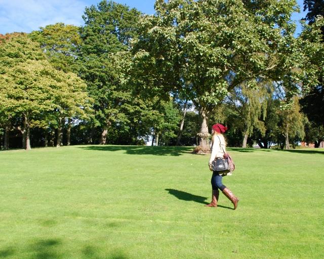 Little Miss Katy walking across a park
