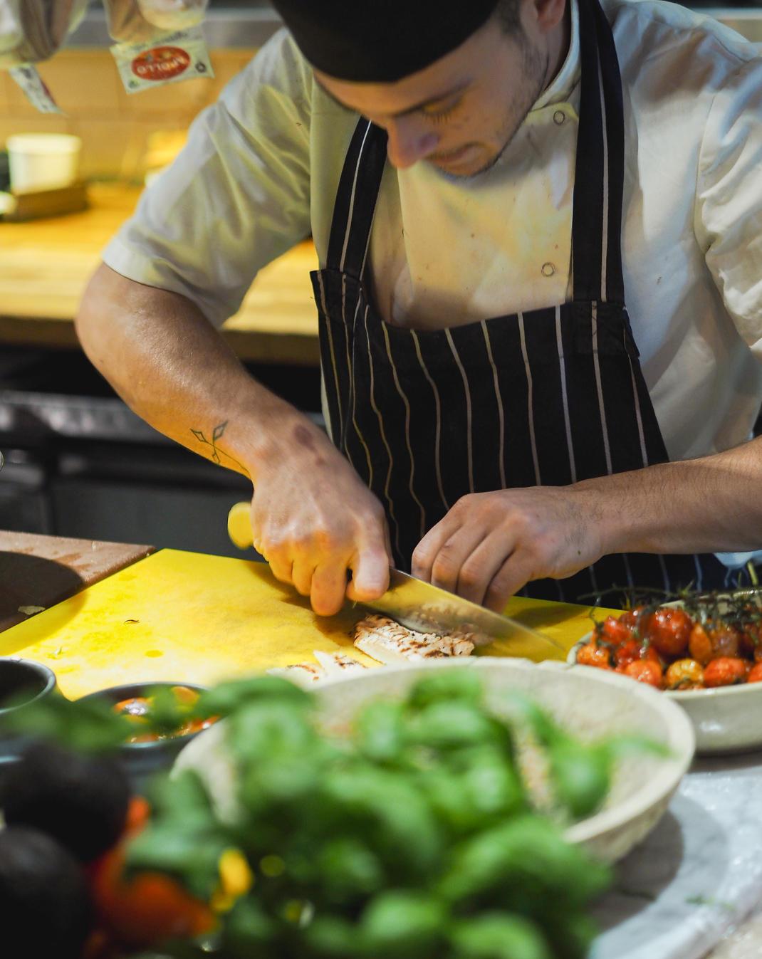 chef slicing chicken breast